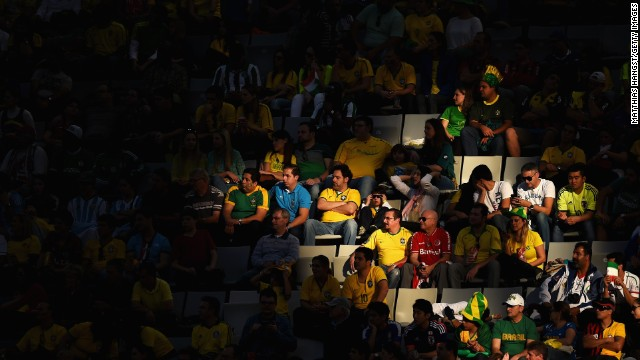 Fans look on from a spot of sunlight during the match between Iran and Nigeria.