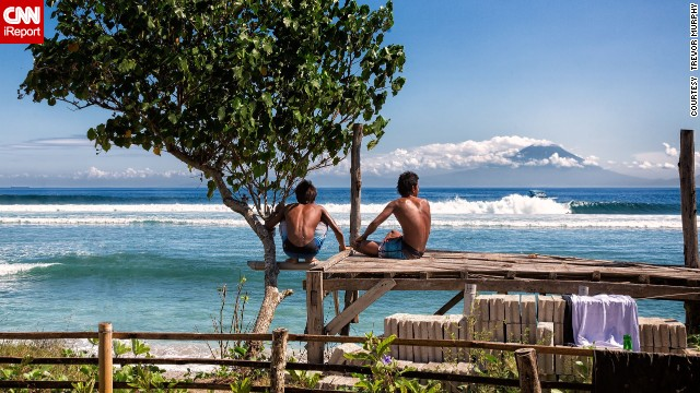 Two surfers survey the waves in Desert Point, Lombok, Indonesia. The spot is known for its massive waves and amazing view of Mount Agung, an active volcano and the highest point in Bali.