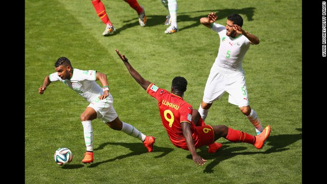El Arabi Soudani of Algeria dribbles past Belgium's Romelu Lukaku.