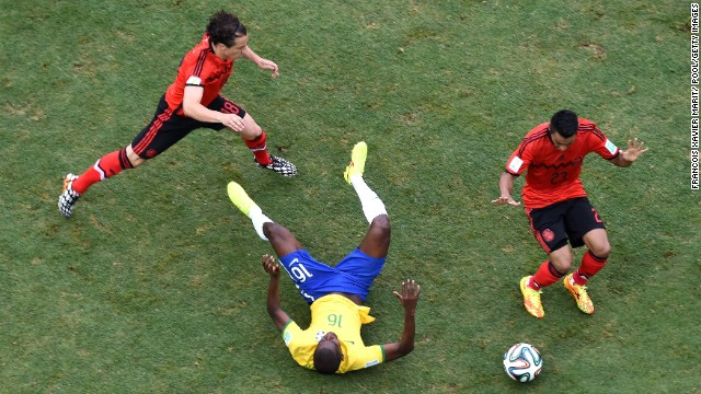 Ramires of Brazil falls after a challenge by Guardado, left, and Vazquez.