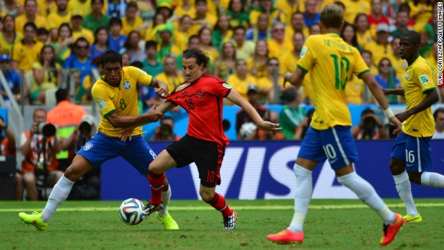 Paulinho, left, battles for the ball with Guardado.