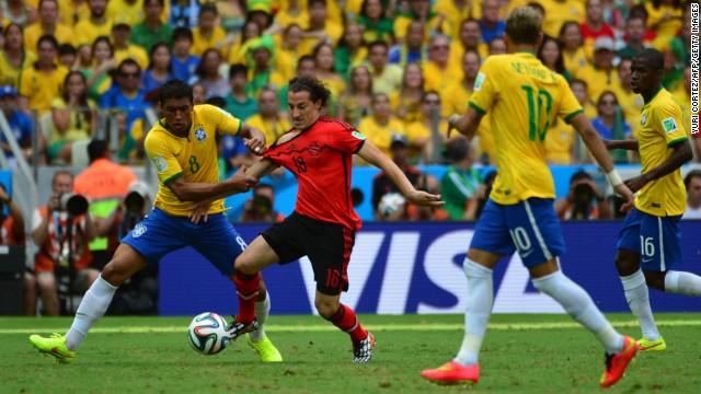 Paulinho, left, battles for the ball with Guardado.