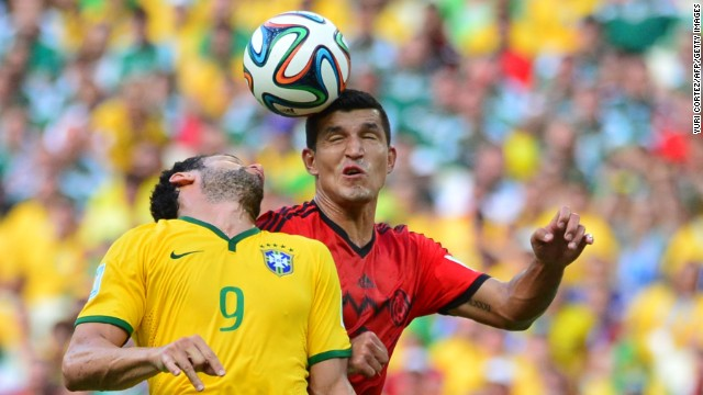 Brazilian forward Fred, left, vies for the ball with Mexican defender Francisco Rodriguez.