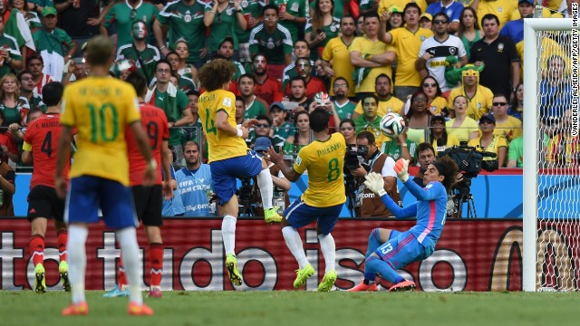 Mexican goalkeeper Guillermo Ochoa, right, makes a save near Brazilian players David Luiz and Paulinho during a World Cup match in Fortaleza, Brazil. The match ended 0-0 in large part to Ochoa, who made several key saves.