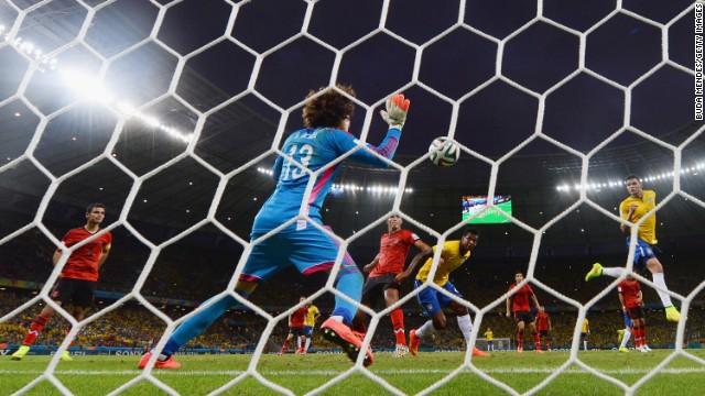 Ochoa makes a save after a header by Brazil's Thiago Silva, right.
