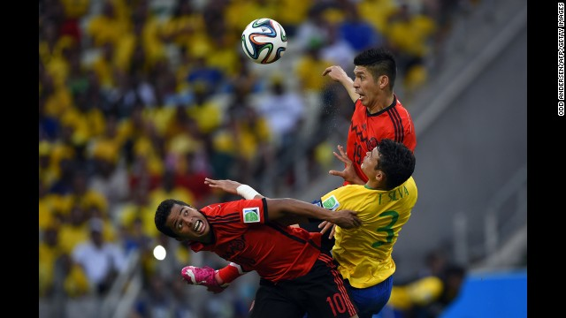 Mexican forwards Giovani Dos Santos, left, and Oribe Peralta try to win the ball with Thiago Silva in between them.
