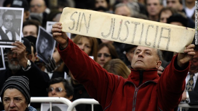 "A man shows a placard that reads ""Without Justice"" amid people holding portraits of victims of the terrorist bombing attack on the commemoration of its 18th anniversary, in Buenos Aires on July 18, 2012."