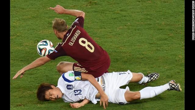 South Korean forward Koo Ja-Cheol, bottom, vies with Russian midfielder Denis Glushakov.