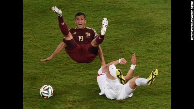 Russian forward Alexander Samedov, left, and South Korean midfielder Ki Sung-Yueng fall during the game.