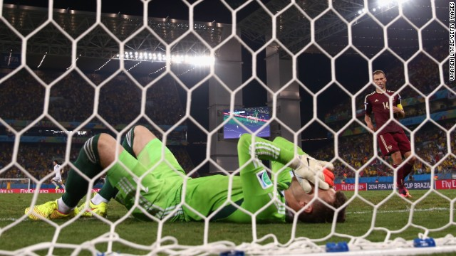 Igor Akinfeev of Russia lies in the net after failing to stop Lee from scoring.