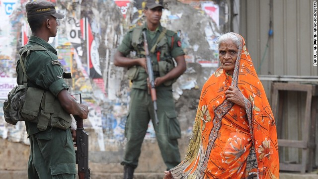 A Sri Lankan Muslim woman walks past soldiers following clashes between Muslims and Buddhists in the town of Aluthgama.