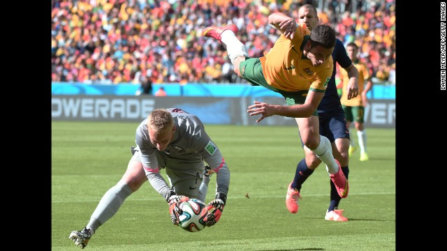 Netherlands goalkeeper Jasper Cillessen corrals the ball while Australia's Mathew Leckie leaps through the air.