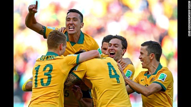 Australian players mob captain Mile Jedinak after Jedinak's penalty kick gave them a 2-1 lead in the second half.