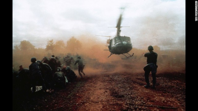 Tim Page photographed a U.S. helicopter taking off from a clearing near Du Co SF camp in Vietnam in 1965. Wounded soldiers crouch in the dust of the departing helicopter. The military convoy was on its way to relieve the camp when it was ambushed.