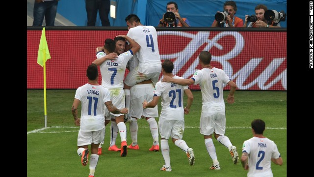 Chilean players celebrate together after midfielder Charles Aranguiz gave them a 2-0 lead against Spain. Chile won the match by that score, eliminating the defending world champions from the soccer tournament.