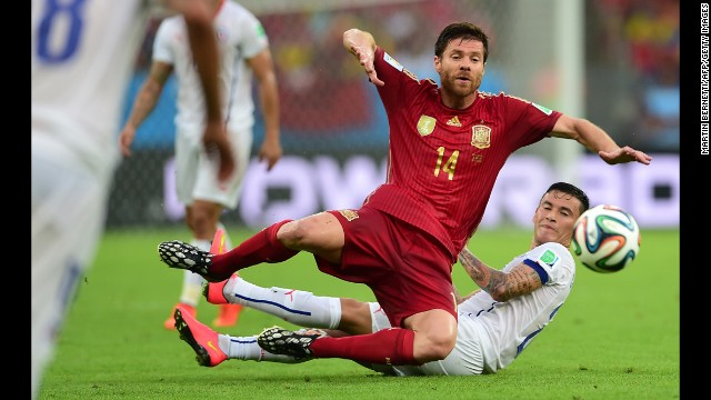 Spanish midfielder Xabi Alonso, left, falls to the ground near Chilean midfielder Charles Aranguiz.
