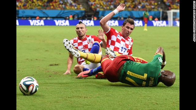 Cameroon's Stephane Mbia falls to the ground as he is challenged by Croatia's Danijel Pranjic, left, and Mario Mandzukic.