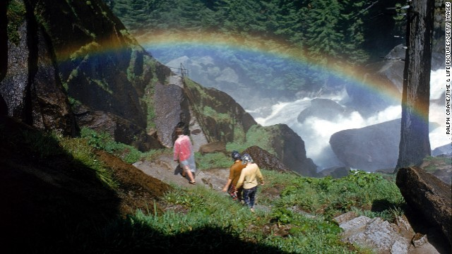 Hikers walk past a rainbow caused by mist from Vernal Falls, circa 1962. There are <a href='http://www.nps.gov/yose/planyourvisit/hiking.htm' target='_blank'>800 miles of trails</a> at the park.
