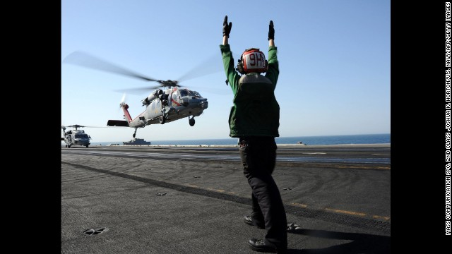 "An MH-60R Sea Hawk helicopter lands on the aircraft carrier USS George H.W. Bush in the Persian Gulf on Tuesday, June 17. The carrier moved into the region to give President Barack Obama ""additional flexibility,"" the Pentagon has said."