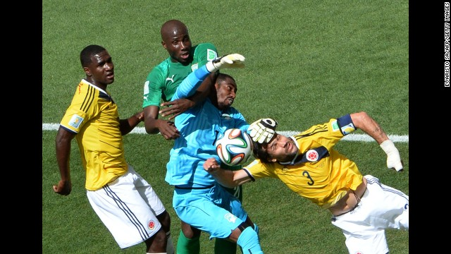 Ivory Coast goalkeeper Boubacar Barry, center, fights for the ball with Colombia defender Mario Yepes, right.