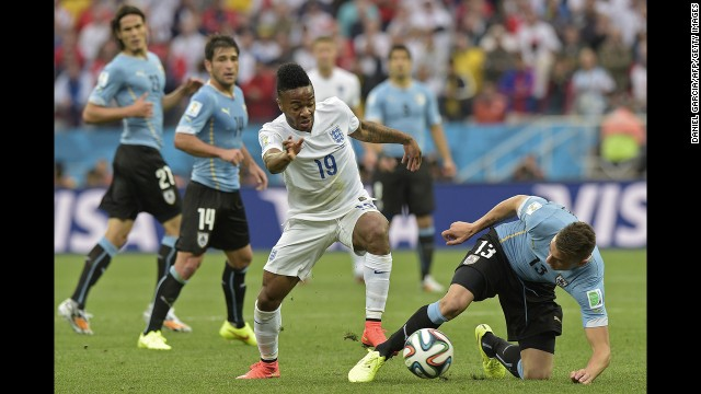 England's Raheem Sterling tries to dribble away from Uruguay defender Jose Maria Gimenez, right.