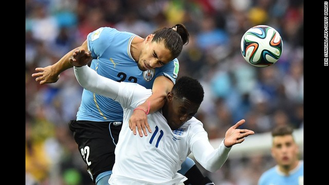 Caceres heads the ball away from England's Danny Welbeck.