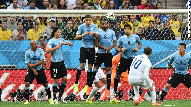Rooney tries to curl a free kick around Uruguayan defenders.