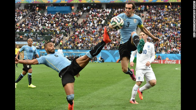 Uruguay midfielder Alvaro Pereira, left, and teammate Diego Godin reach for the ball in the first half.