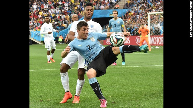 Uruguay midfielder Cristian Rodriguez shields the ball from Sterling.