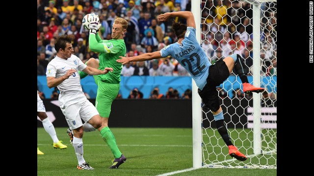 Hart makes a save as Uruguay defender Martin Caceres flies past the goal.