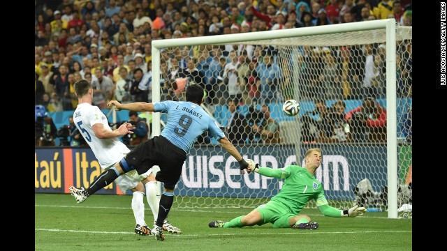 Suarez blisters a shot past England goalkeeper Joe Hart.