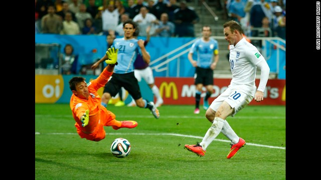Rooney slips the ball past Uruguay goalkeeper Fernando Muslera.