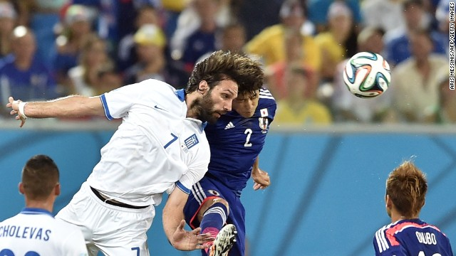 Greece forward Georgios Samaras, left, and Japan defender Atsuto Uchida compete for the ball.