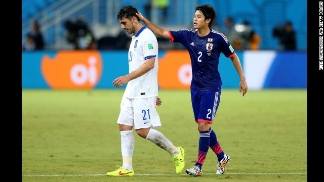 Konstantinos Katsouranis of Greece is consoled by Atsuto Uchida of Japan after he received a red card.