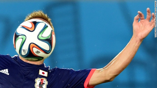 Japan forward Keisuke Honda heads the ball.