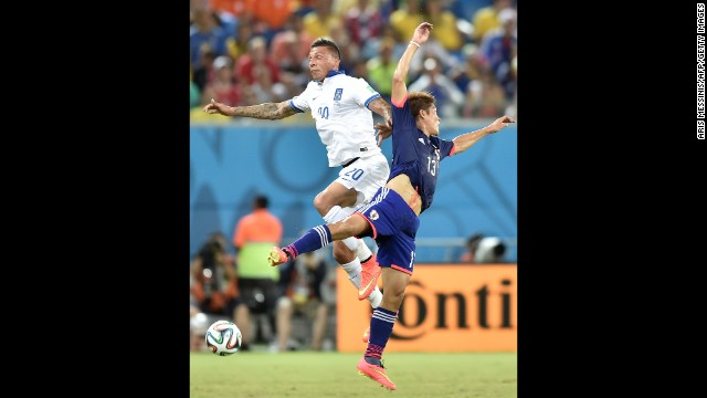 Greece defender Jose Holebas, left, vies for the ball against Japan forward Yoshito Okubo.