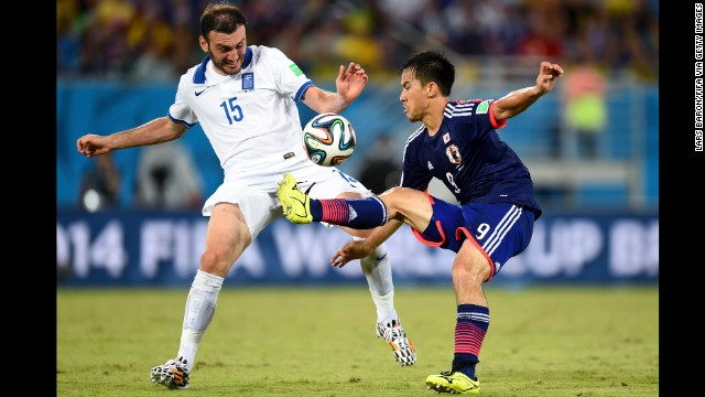 Vasilis Torosidis of Greece and Shinji Okazaki of Japan compete for the ball