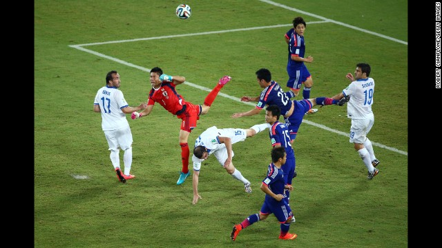 Goalkeeper Eiji Kawashima of Japan punches the ball clear as Vasilis Torosidis of Greece and Maya Yoshida of Japan collide.
