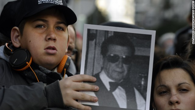 A boy holds a picture of a victim during a memorial parade in Buenos Aires in 2012.