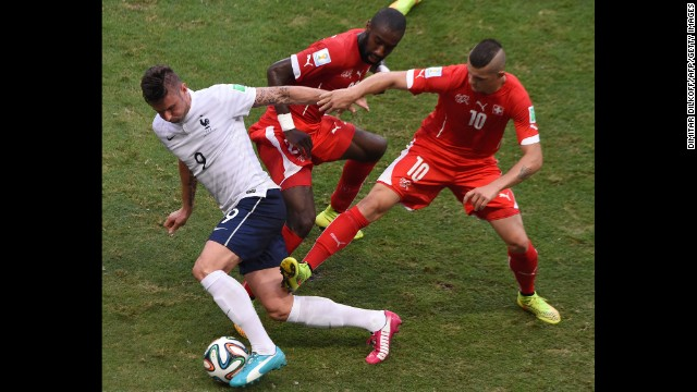French forward Olivier Giroud, left, dribbles past two Swiss players.