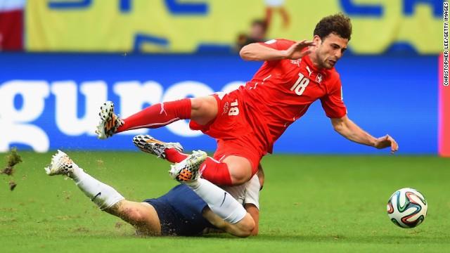 Admir Mehmedi of Switzerland and Mathieu Debuchy of France collide.