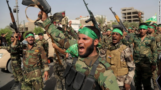 """Peace Brigade"" volunteers raise their weapons and chant slogans during a parade in the Shiite stronghold of Sadr City on Saturday, June 21, in Baghdad. The armed group was formed to protect Shiite holy shrines against possible attacks by Sunni militants."