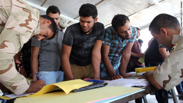 Iraqi men register to fight alongside security forces Friday, June 20, at a recruitment center in Baghdad.