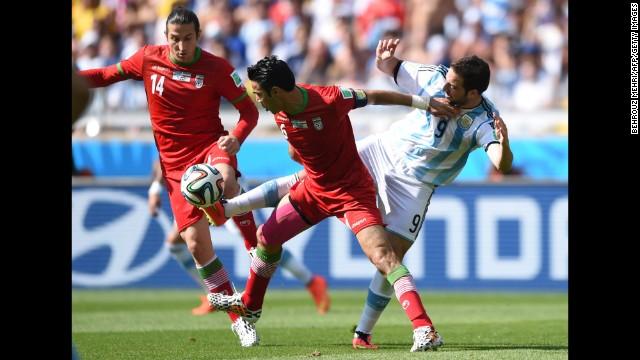 Iran midfielders Andranik Teymourian and Javad Nekounam battle for the ball against Argentina forward Gonzalo Higuain.