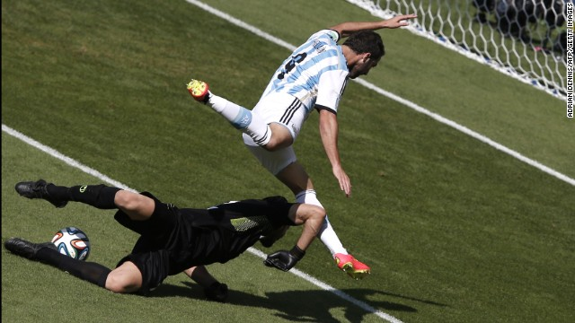 Argentina forward Gonzalo Higuain, right, and Iran's goalkeeper Alireza Haqiqi vie for the ball.