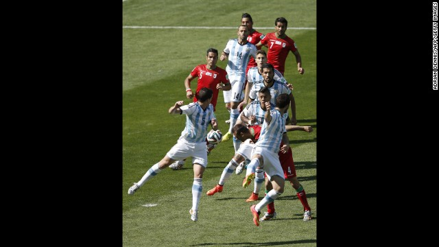 Iran defender Jalal Hosseini, second right, heads the ball.