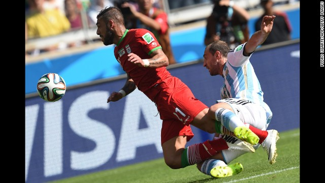 Iran forward Ashkan Dejagah, left, and Argentina defender Pablo Zabaleta collide.
