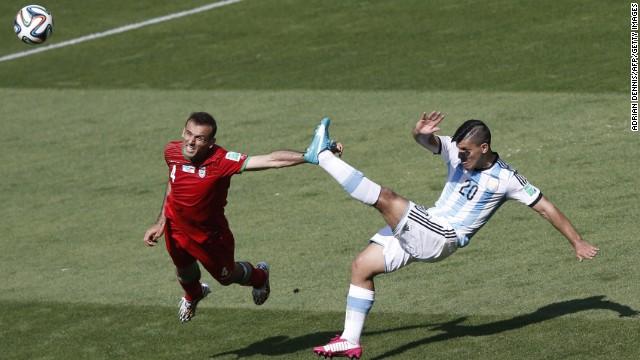 Iran defender Jalal Hosseini, left, and Argentina forward Sergio Aguero vie for the ball.