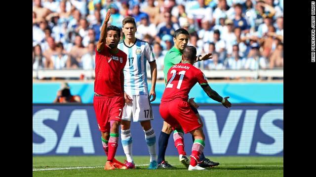 Members of the Iranian team appeal to referee Milorad Mazic, claiming Argentina's Pablo Zabaleta fouled Ashkan Dejagah of Iran.