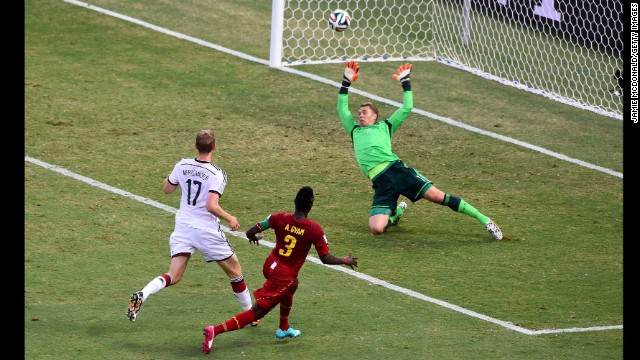 Asamoah Gyan of Ghana scores his team's second goal past Manuel Neuer of Germany.